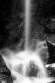 White waterfall splashing onto black rocks.