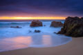 Dusk light glows off the ocean and rocks and wet sand.