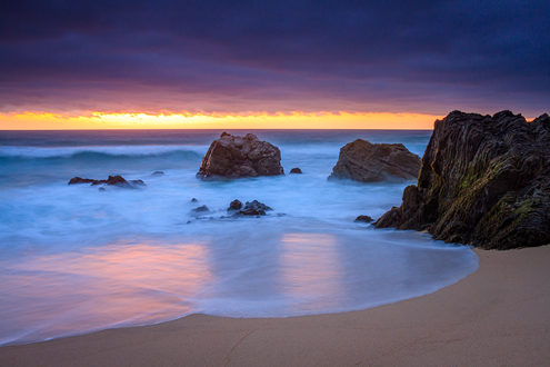 The sun sets behind a low purple cloud bank leaving a sliver of golden light washed across the wet rocks, sand and surf at this Big Sur beach.