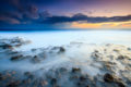 Misty surf washes over volcanic rocks lining the beach with twilight colors in the sky.