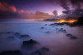 Twilight long exposure with misty surf on a rocky beach with distant city lights.