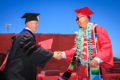 College president shakes hands with a MPC graduate on stage and gives him his diploma.