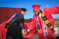 College president slaps hands with a MPC graduate on stage.