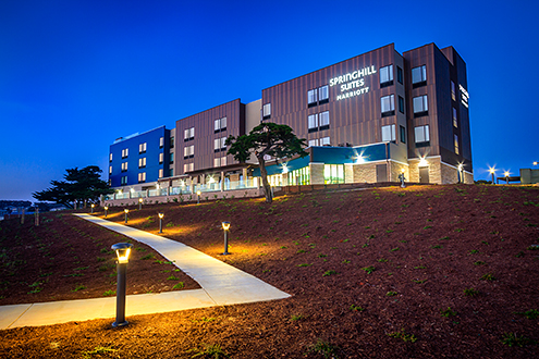 Exterior view of the western facing side of a Marriott Hotel with deep blue twilight sky in the background and a lit path winding up to it.