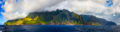 The Kauai island as seen from a boat on the ocean with bright-colored foliage and cloud-shrouded mountains.