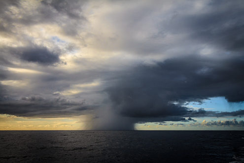 Very localized rain storms are common off the Na Pali Coast of Hawaii. There were a number of squalls passing by along the horizon as sunset approached.