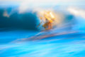 Multiple exposure of a surfer bathed in sunset light racing across a crashing wave.