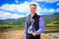 Volunteer of the Year Award recipient poses with his award in from of SLH vineyards.