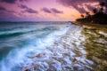 Hawaiian sunset with waves washing over volcanic rock tide pools.