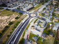 Streetscape of a roundabout intersection in a suburban neighborhood shot with a drone camera.