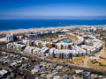 Drone photo of a city-block-size apartment complex near the beach and a pier.