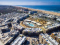 Drone photo of a city-block-size apartment complex near the beach under construction.