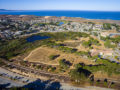 Drone photo of a park with library, trees, trails, and large pond sourounded by homes, san dunes, and the ocean.